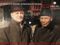 A white man and a black man in coats and hats standing outside a window with a neon signe.