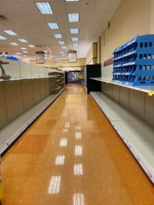 View down a grocery aisle with empty shelves.