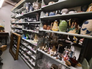 Aisle of metal shelving with a wide variety of objects on it including pottery, vases, bells, china and silver.