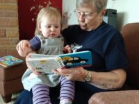 elderly woman reading to a child