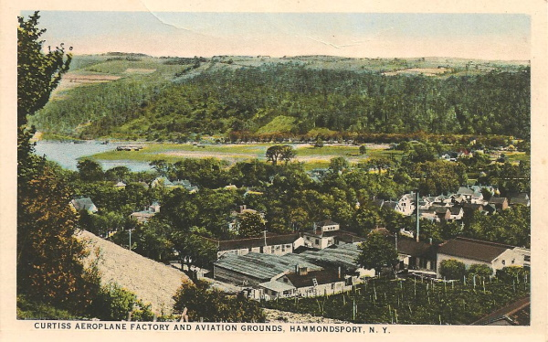 Postcard from a hill showing a factory and houses in a wooded valley and near a lake.