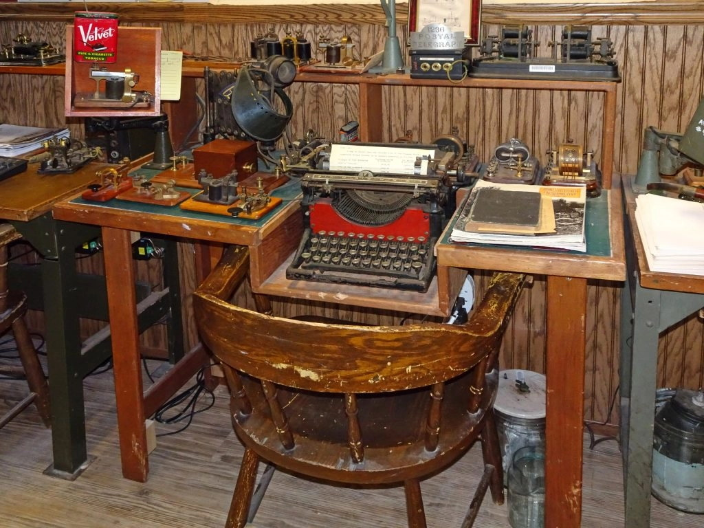 A small wooden desk with a typewriter and telegraph machines on it and and banker's chair in front of it.